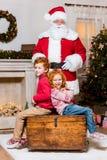 Papai Noel e irmãos pequenos Imagem de Stock Royalty Free