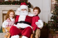 Papai Noel e irmãos pequenos Fotos de Stock Royalty Free
