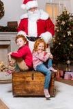 Papai Noel e irmãos pequenos Fotografia de Stock Royalty Free