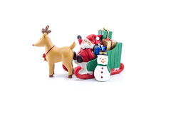 Papai Noel em levar do trenó presentes com rena e boneco de neve Foto de Stock