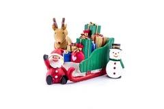 Papai Noel em levar do trenó presentes com rena e boneco de neve Fotografia de Stock Royalty Free