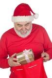 Papai Noel engraçado que toma um presente de seu saco Imagem de Stock Royalty Free