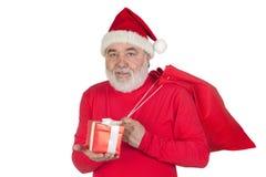 Papai Noel engraçado com um presente e seu saco Foto de Stock