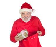 Papai Noel engraçado que toma um presente de seu saco Fotos de Stock Royalty Free