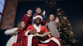 Papai Noel feliz no chapéu vermelho e quatro nas crianças bonitos que acenam à câmera video estoque