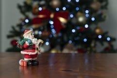 Papai Noel no fundo de madeira com a árvore de Natal no fundo imagem de stock