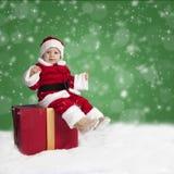 Papai Noel pequeno assentado em um presente de Natal na neve imagens de stock