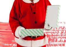 Papai Noel que abre seu presente do Natal fotografia de stock