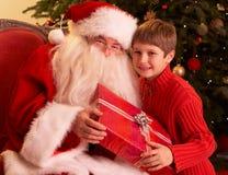 Papai Noel que dá o presente ao menino na frente de Christm Fotos de Stock