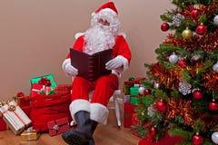 Papai Noel que lê a lista Fotos de Stock