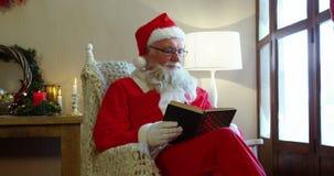 Papai Noel que olha através da janela ao ler uma novela video estoque