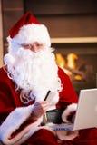 Papai Noel que paga com cartão de crédito Fotografia de Stock