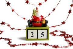 Papai Noel que senta-se nos cubos que mostram a data 25 de dezembro no fundo branco com festão vermelha Foto de Stock Royalty Free