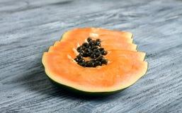 Papaia affettata su fondo di legno Immagini Stock Libere da Diritti