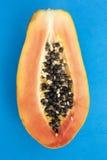 Papaia cortada em um fundo azul Fotografia de Stock Royalty Free