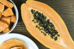 A papaia cortou ao meio com partes na bacia Imagem de Stock
