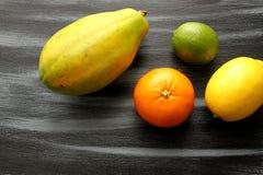 Papaja, Citroen, kalk en bloedsinaasappel op zwarte raad Royalty-vrije Stock Foto's