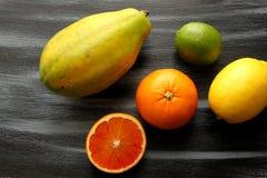 Papaja, Citroen, kalk en bloedsinaasappel op zwarte raad Stock Fotografie