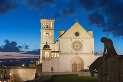 The Papal Basilica of St. Francis of Assisi after sunset. Silhouette of statue of St. Francis on horseback is in the foreground. (Assisi, Umbria, Italy Royalty Free Stock Image