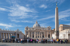 The Papal Basilica of St. Peter. Vatican, Italy - November 7, 2015: The Papal Basilica of St. Peter against blue sky and its square with tourists stock photography