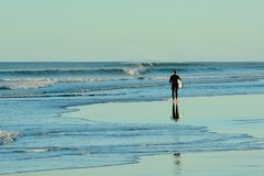 Papamoa Beach, Papamoa, New Zealand, July 07, 2019: an unidentified surfer preparing to enter the sea. Holidays at the sea; winter time in New Zealand; surfing royalty free stock photos