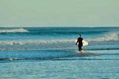 Papamoa Beach, Papamoa, New Zealand – July 07, 2019: an unidentified surfer preparing to enter the sea. Holidays at the sea; winter time in New Zealand stock photography