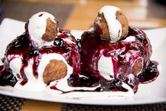 Papanasi - a traditional Romanian dessert. The cake is made from three donuts covered in sour cream and fruits jam stock photos