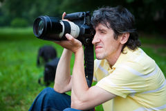 Paparazzi. Man photographs the professional camera Stock Images