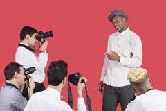 Paparazzi die foto's van mannelijke acteur over rode achtergrond nemen Royalty-vrije Stock Afbeeldingen