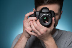 Paparazzi man taking picture with photo camera. Stock Image