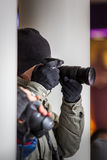 Paparazzi photographer hiding and taking pictures among building Royalty Free Stock Photo