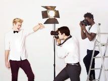 Paparazzi que tomam fotografias do ator masculino sobre o fundo branco Fotografia de Stock Royalty Free