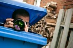 Paparazzi se cachant dans une poubelle de déchets bleue Image stock