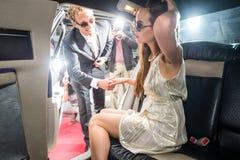 Paparazzi som fotograferar den manliga kändisen som hjälper hans flickvän till Arkivfoto