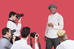 Paparazzi taking photographs of male actor over red background Royalty Free Stock Images
