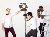 Paparazzi taking photographs of male actor over white background Royalty Free Stock Photography