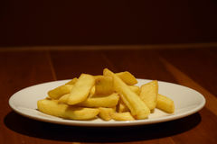 Papases fritas de oro en la placa blanca en la tabla de madera Fotografía de archivo