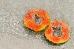 Papaya, χέρι, φέτα, τροπικά φρούτα, θάλασσα, άμμος στοκ φωτογραφία