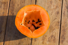 Papaya on brown wood table. Half of papaya with seeds on brown wooden talbe stock image