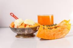Papaya con helado en el fondo blanco imagen de archivo