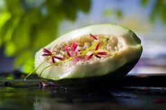 Papaya cruda en superficie mojada con la tierra trasera verdosa Fotos de archivo libres de regalías