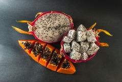 Papaya and dragon fruit served for a dessert on black background Stock Photos