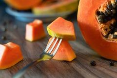 Papaya en una tabla de cocina y pedazo de papaya en una bifurcación imágenes de archivo libres de regalías