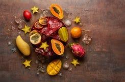 Papaya för tropiska frukter, drakefrukt, rambutan, tamarindfrukt, granadilla, carambola, mango med iskuber på ett mörker Royaltyfri Fotografi
