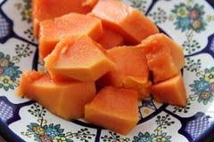 Papaya fruit or fruta bomba. Piece of ripe papaya fruit on Talavera ceramic - mexican traditional plate, ready to eat Royalty Free Stock Images