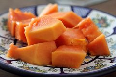 Papaya fruit or fruta bomba. Piece of ripe papaya fruit on Talavera ceramic - mexican traditional plate, ready to eat Royalty Free Stock Photography
