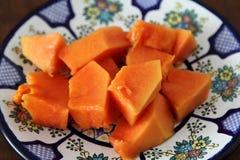 Papaya fruit or fruta bomba. Piece of ripe papaya fruit on Talavera ceramic - mexican traditional plate, ready to eat Royalty Free Stock Image
