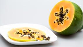 Papaya fruit - half and slice with seeds Royalty Free Stock Photography