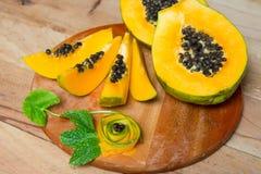 Papaya fruit on wooden background. Sliced fresh papaya. Papaya fruit on wooden background Royalty Free Stock Photo