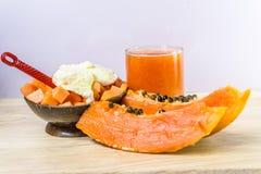 Papaya, fruktsaft och glass för öken på träbakgrund Royaltyfri Foto